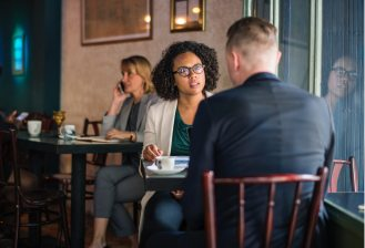 interview, black woman in interview, two people by window, lady on phone, in a coffee shot